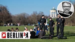 Polizisten lösen eine Menschengruppe im Englischen Garten in München auf