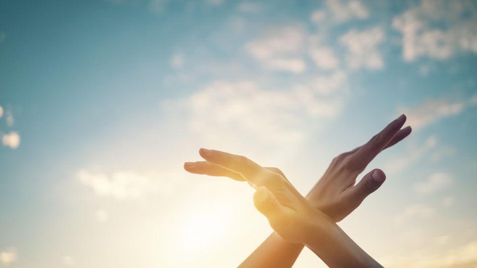 Frau hält Hände in den Himmel