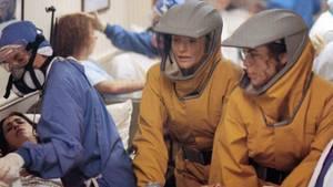 """Gespenstisch realistisch: Eine Szene aus """"Outbreak"""", in denen sich die Darstellerinnen Rene Russo undSusan Lee Hoffman in Schutzanzügen um infizierte Patienten kümmern."""