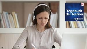 Eine junge Frau sitzt mit Kopfhörern am Rechner und schreibt einen Brief