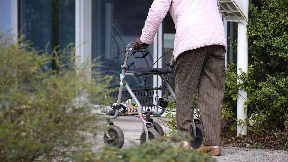 Bayern, Würzburg: Ein ältere Frau mit Rollator geht vor dem Eingang eines Senioren-Wohnstiftes