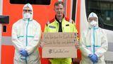 """#FlattenTheCurve: Ein Notarzt hält,eingerahmt von zwei Rettungssanitätern in Infektionsschutzkleidung,ein Schild mit der Aufschrift """"Wir bleiben für euch da! Bleibt für uns daheim!""""."""