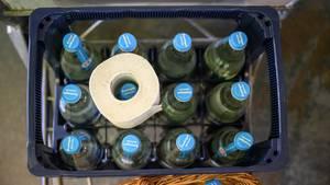 Eine Rolle Klopapier liegt auf einer Kiste mit leeren Wasserflaschen