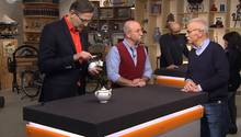 """""""Bares für Rares""""-Experte Detlev Kümmel untersucht die Milchkanne, Moderator Horst Lichter lässt sich von Verkäufer Uwe Fischer die Herkunft der beiden Stücke erklären."""