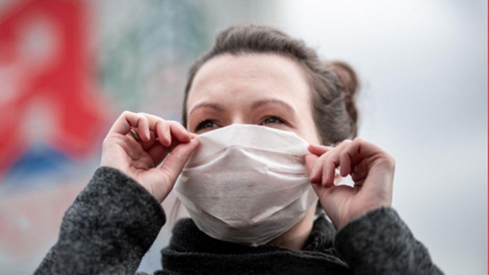 Eine Frau trägt vor einer Apotheke eine Mund- und Nasenmaske