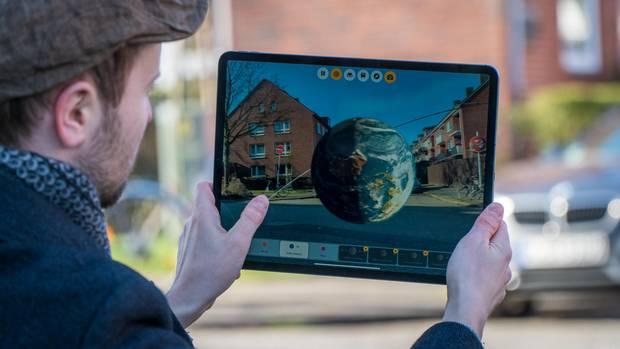 Ein Fingertipp, schon sieht man ein Modell der Erde mitten auf der Straße: Apple denkt, dass Augmented-Reality-Apps das Lernen revolutionieren könnten.