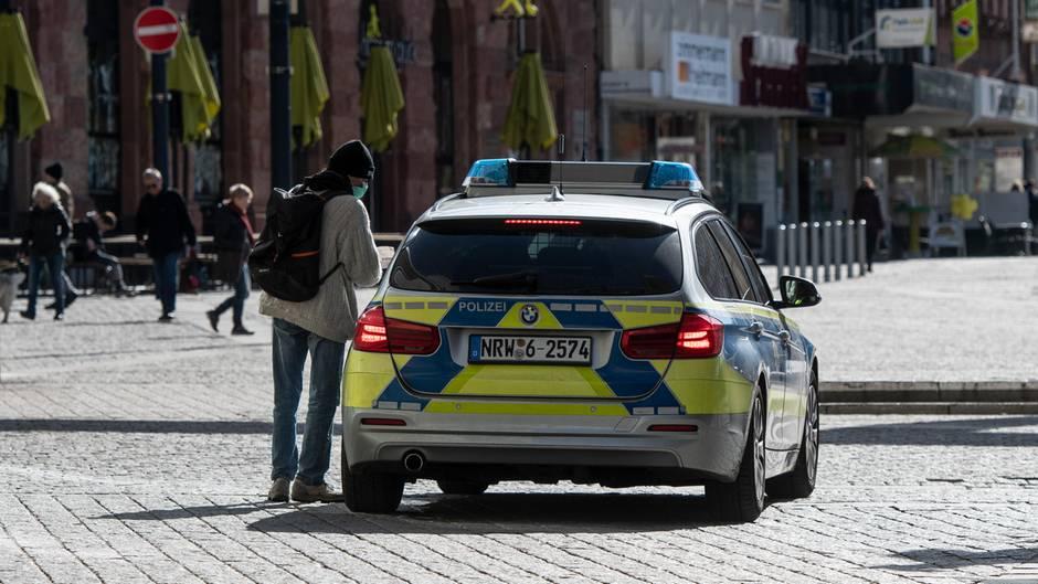 Ein Mann mit einem Mundschutz unterhält sich in der Fußgängerzone mit den Polizisten in einem Streifenwagen