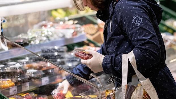 Eine Frau kauft mit Handschuhen im Edeka ein
