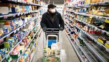 Ein Mann mit Mundschutzmaske kauft im Supermarkt ein