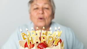 Ältere Frau pustet Kerzen auf dem Geburtstagskuchen aus