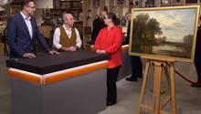"""""""Bares für Rares""""-Experte Detlev Kümmel und Moderator Horst Lichter lassen sich von Verkäuferin Vera Schenk die Herkunft ihres Gemäldes erklären."""