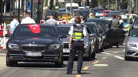 In Köln steht eine Polizistin vor den Fahrzeugen eines angehaltenen türkischen Hochzeutskorsos