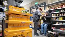 Eine Rewe-Mitarbeiterin hilft einem älteren Menschen beim Einkauf