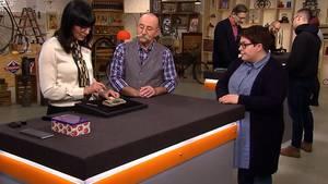 """""""Bares für Rares""""-Expertin Heide Rezepa-Zabel erklärt die Stickereien auf der Tasche. Moderator Horst Lichter und VerkäuferinMartina Riedemann hören zu."""