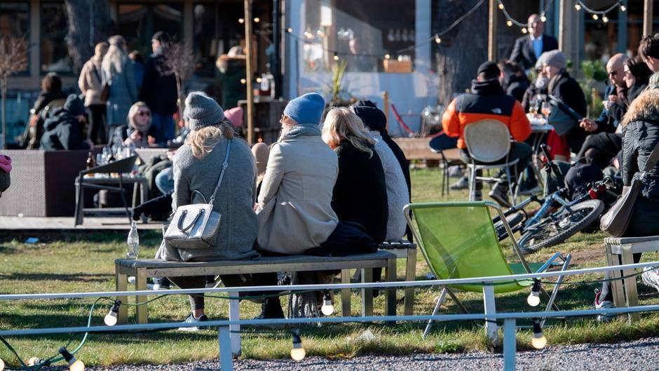 Menschen genießen das sonnige Wetter in einem Restaurant im Freien in Djurgarden in Stockholm