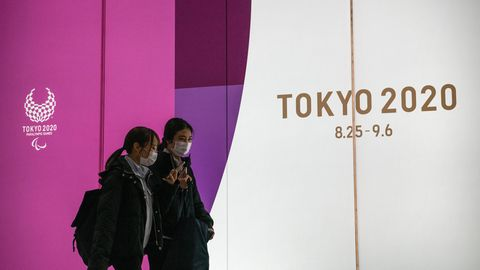 Zwei Frauen mit Atemmasken gehen in Tokio an Werbung für Olympia 2020 vorbei