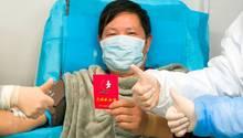 China, Wuhan: Ein genesener Coronavirus-Patient hält