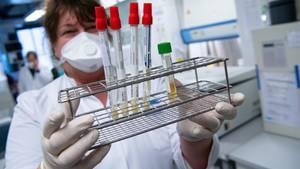 Laborant mit Reagenzgläsern in der Hand