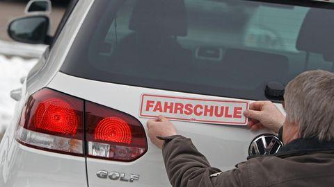 """Ein Fahrlehrer bringt ein Schild mit """"Fahrschule"""" am Kofferraum an"""