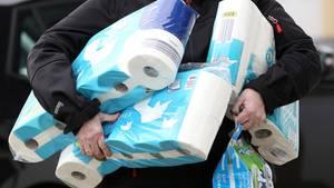 Eine Person trägt mehrere Pakete Toilettenpapier unter dem Arm