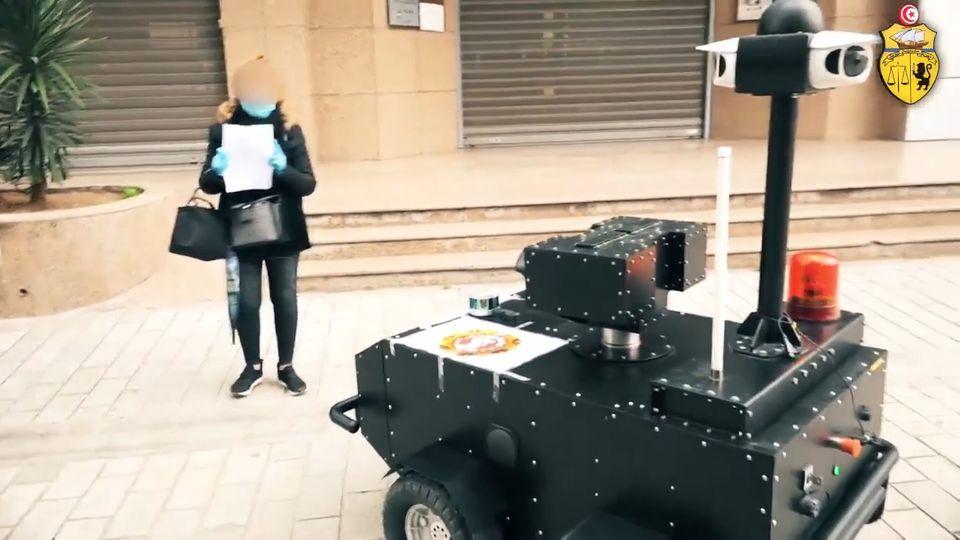 Coronavirus in Tunesien: Eine Frau zeigt einem Polizeiroboter ihre Bescheinigung bei Ausgangsbeschränkungen in Tunis