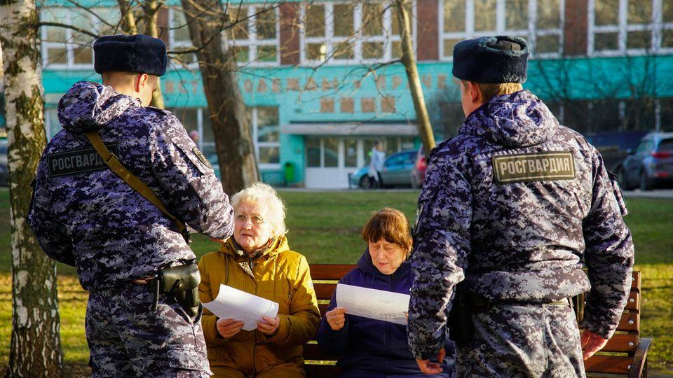 Moskau: Russische Soldaten der Nationalgarde sprechen mit zwei Rentnerinnen auf einer Parkbank.