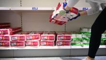 Eine Mitarbeiterin füllt leere Toilettenpapier-Regale auf