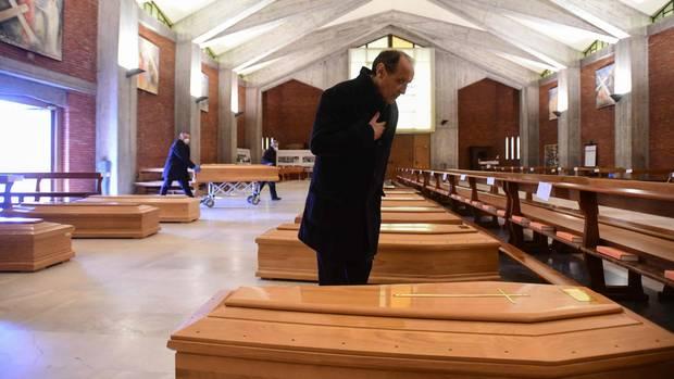 Don Mario spricht Gebete für zahlreiche Corona-Tote, die in der Kirche seiner Stadt aufgebahrt wurden