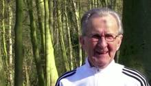 Ein älterer Mann mit weißen, zurückgekämmten Haaren steht in weißer Trainingsjacke in einem sonnendurchfluteten Wald