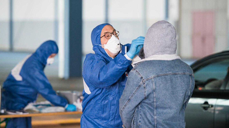 Test auf das Coronavirus: Ein Arzt nimmt in einer Halle der ehemaligen Saarbrücker Messe einen Abstrich