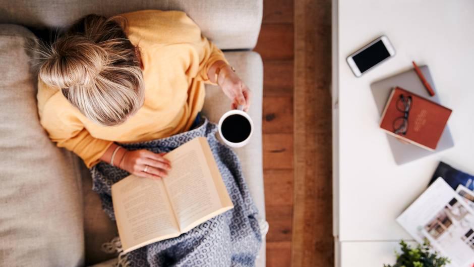 Frau sitzt mit einem Buch und einer Tasse Kaffee im Bett