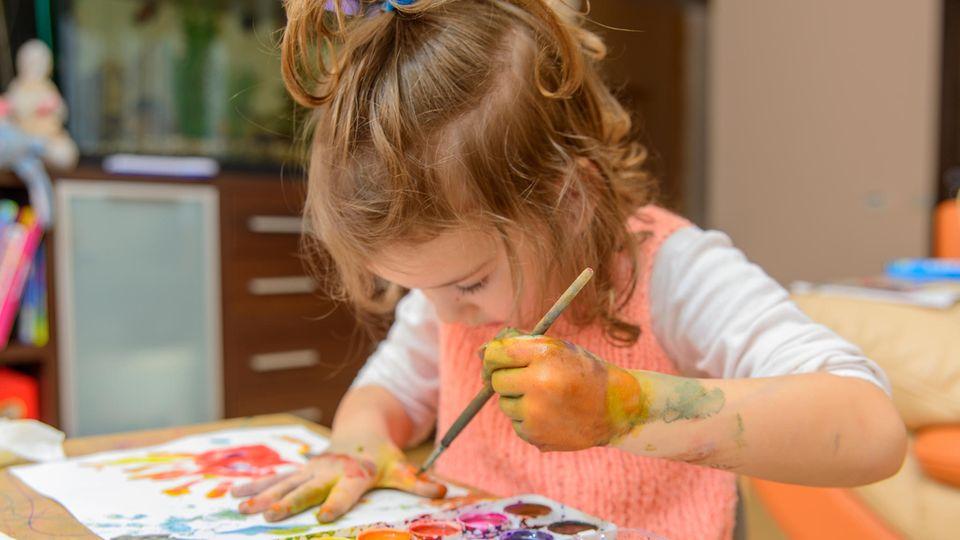Ein Mädchen malt sich die Hände an