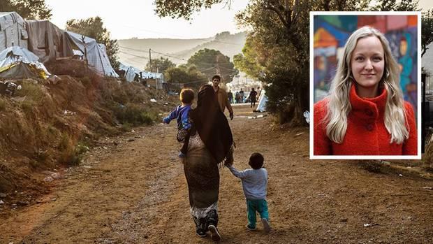 Eine Frau mit 2 Kindern läuft durch das Camp, ein Mann kommt ihr entgegen, daneben Zoe im roten Pulli vor einer bunten Wand