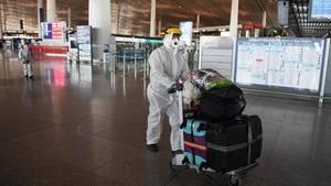 Ein Reisender in Schutzkleidung am Flughafen Peking