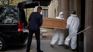 Sargträger, die ihr Gesicht mit Masken gegen das Coronavirus schützen, tragen einen Sarg auf dem Friedhof von Barcelona