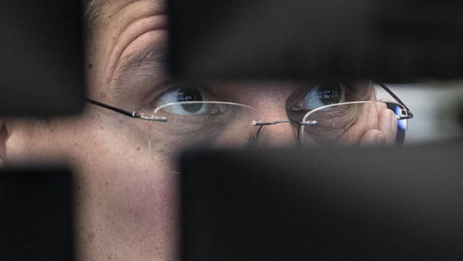 Ein Börsenhändler an der Börse Frankfurt blickt auf seine Monitore