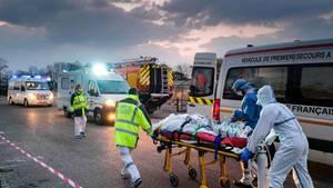 Frankreich, Mulhouse: Medizinisches Notfallpersonal transportiert einen Patienten, der mit dem Coronavirus infiziert ist