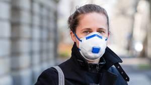 Coronavirus: Eine Frau steht auf der Straße und trägt eine Atemschutzmaske