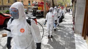 Spanien, Barcelona: Soldaten in Schutzanzügen gehen mit Abstand in Richtung eines Seniorenheims