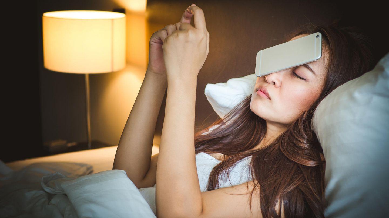Eine Frau liegt mit einem Smartphone, das ihr aus den Händen auf das Gesicht gefallen ist, im Bett