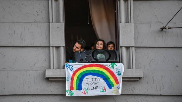"""Menschen schauen hinter Musikbox und Plakat mit der Aufschrift """"Tutto andra bene"""" (dt. Alles wird gut) aus dem Fenster"""