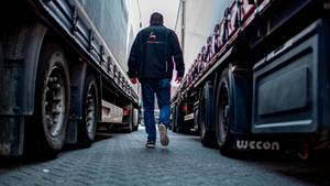 LKW-Fahrer Ronny Knoblauch geht auf dem Autohof zwischen zwei abgestellten LKW hindurch