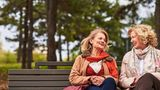 Frauen unterhalten sich auf einer Parkbank