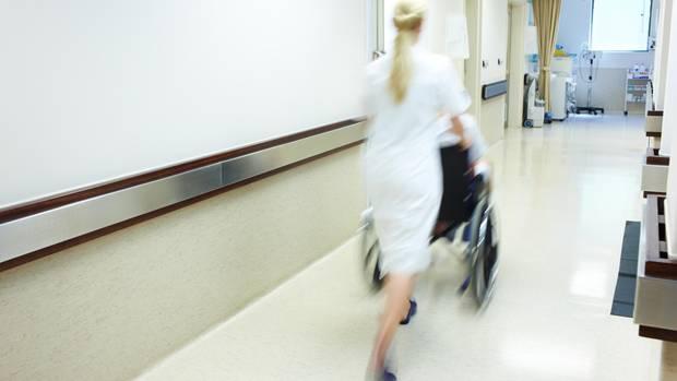 Krankenschwester mit Patient im Rollstuhl