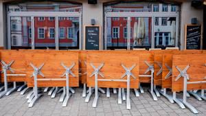 Hochgeklappte Tische stehen in der Fußgängerzone vor einer Gastwirtschaft.
