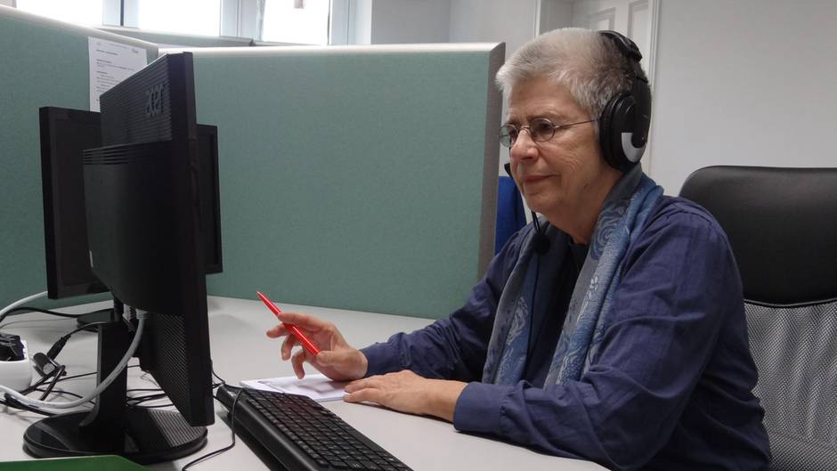 Elke Schilling von Silbernetz mit Kopfhörern am Computer