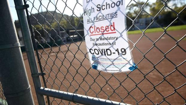 Ein Schild vor einer High School in den USA weist auf die Schließung wegen Covid-19 hin