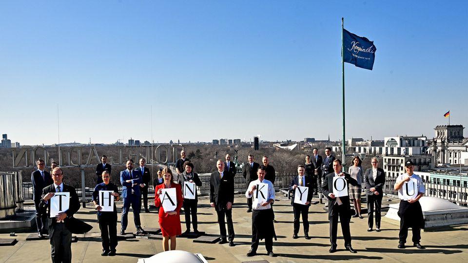 Mitarbeiter auf dem Dachdes Adlon Hotels in Berlin: ein Dankeschön für Krisenhelfer