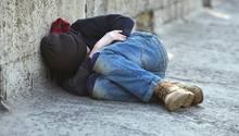 Ein Junge liegt eingerollt auf der Straße