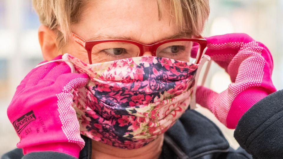 Eine Supermarkt-Mitarbeiterin mit Maske